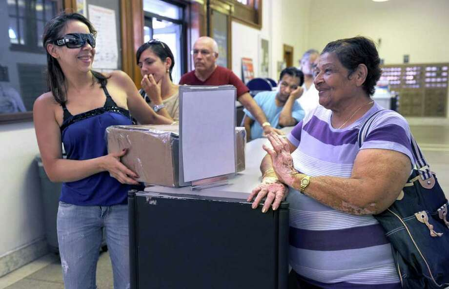 Gertrudis Rodriguez, left, and Aura Ruic both of Danbury, wait in line Wednesday at the Main Street post office. Photo taken Wednesday, July 27, 2011. Photo: Carol Kaliff