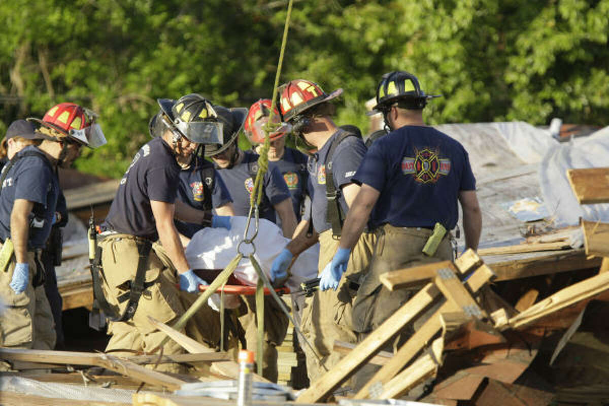 Firefighters work to remove a body that was recovered at the scene.
