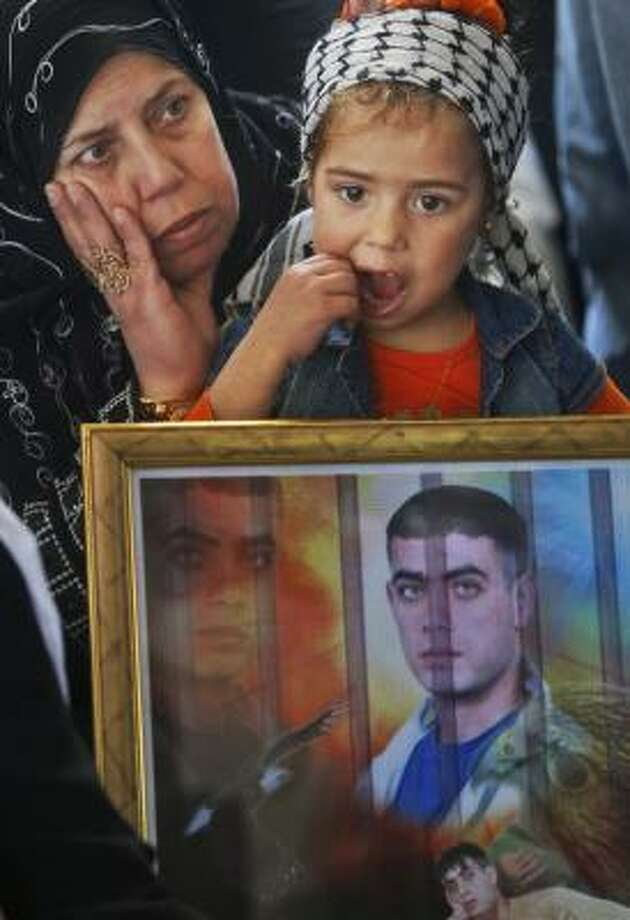 During a protest calling for the release of inmates held in Israeli jails, a Palestinian woman and child hold a picture of an imprisoned relative at the International Red Cross in Gaza City on Monday. Photo: KHALIL HAMRA, Associated Press