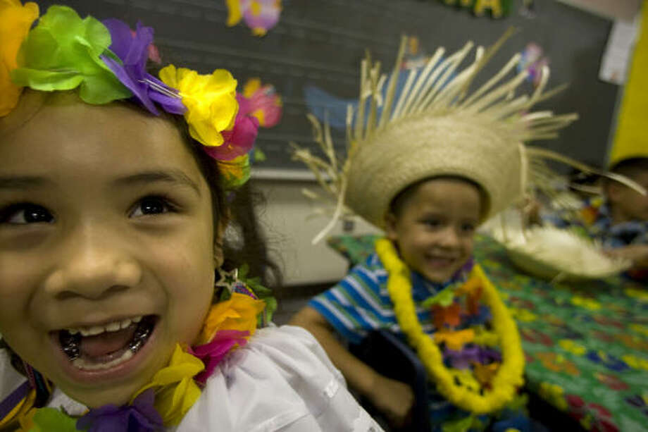"""E.A. """"Squatty"""" Lyons Elementary pre-kindergarten students, Samantha Carrillo, 5, (right) and Nathan Flores, 5, (right) celebrated the end of the school year with a Hawaiian themed luau and awards banquet that included pizza and juice Wednesday, May 27, 2009, in Houston.  Lyons Elementary was one of the schools that lost school days due to the swine flu and Hurricane Ike earlier in the year. ( Johnny Hanson / Chronicle ) Photo: Johnny Hanson, Chronicle"""