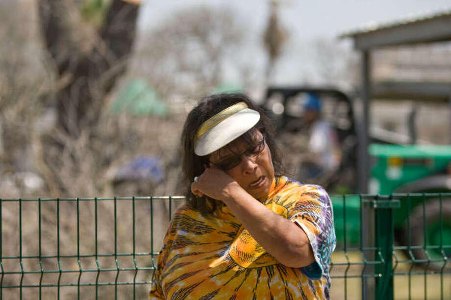 Yolanda Moran, 62, cries as trees begin to come down in Adoue Park. One of the trees to be cut was planted by her father. Photo: Nick De La Torre, Chronicle