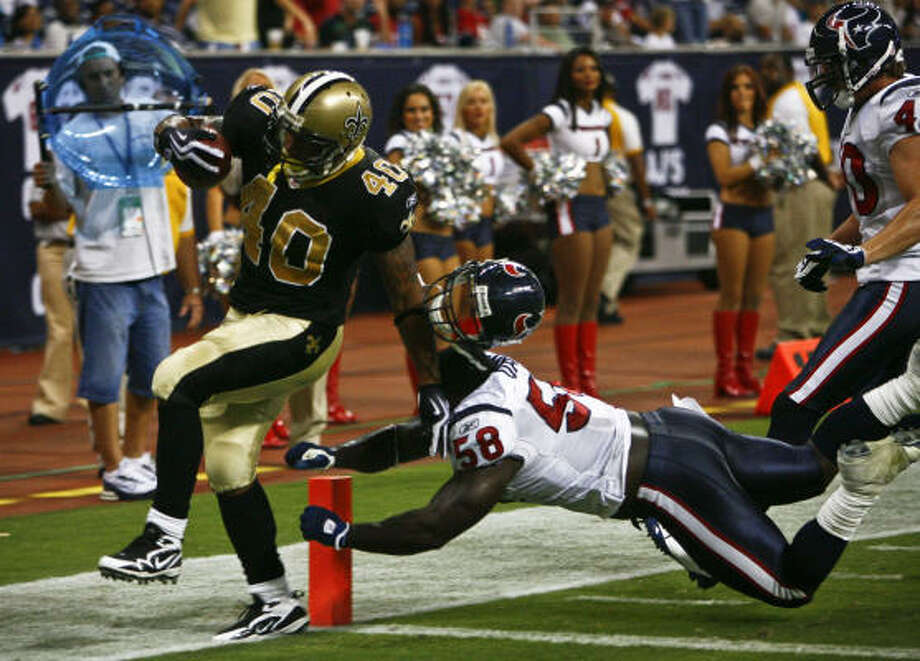 New Orleans' Herb Donaldson scoots into the end zone past Texans linebacker Buster Davis, who loses his helmet while trying to stop the fourth-quarter touchdown run Saturday night. Photo: Michael Paulsen, Chronicle