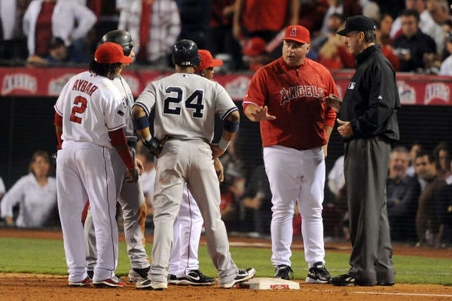 Replays showed third base umpire Tim McClelland, right, missed two calls in Game 4 of the ALCS, one favoring each team. Photo: Harry How, Getty Images