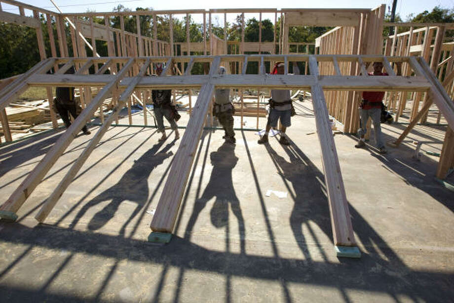 "A crew raises an interior wall on a house being built in the Lake Shore Harbor subdivision in Missouri City. ""In some areas, demand for new homes is even outpacing supply,"" said an official of Metrostudy, which released a housing report Wednesday. Photo: Brett Coomer :, Chronicle"