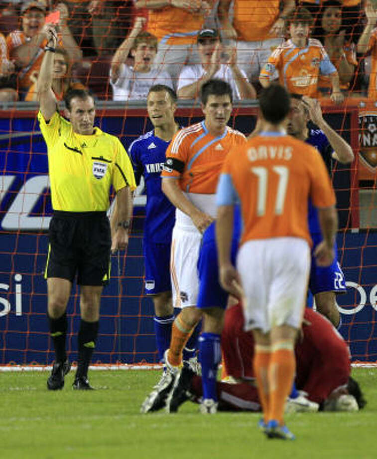 Referee Terry Vaughn calls a red card on Wizards midfielder Davy Arnaud after he ran into Dynamo goalkeeper Pat Onstad, right. Photo: Brett Coomer, Chronicle