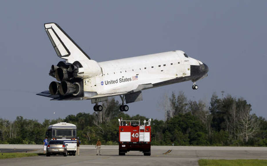 Space shuttle Atlantis glides by rescue vehicles before landing on Kennedy Space Center's runway 33 Wednesday, May 26, 2010 in Cape Canaveral, Fla. (AP Photo/Terry Renna) Photo: Terry Renna, AP