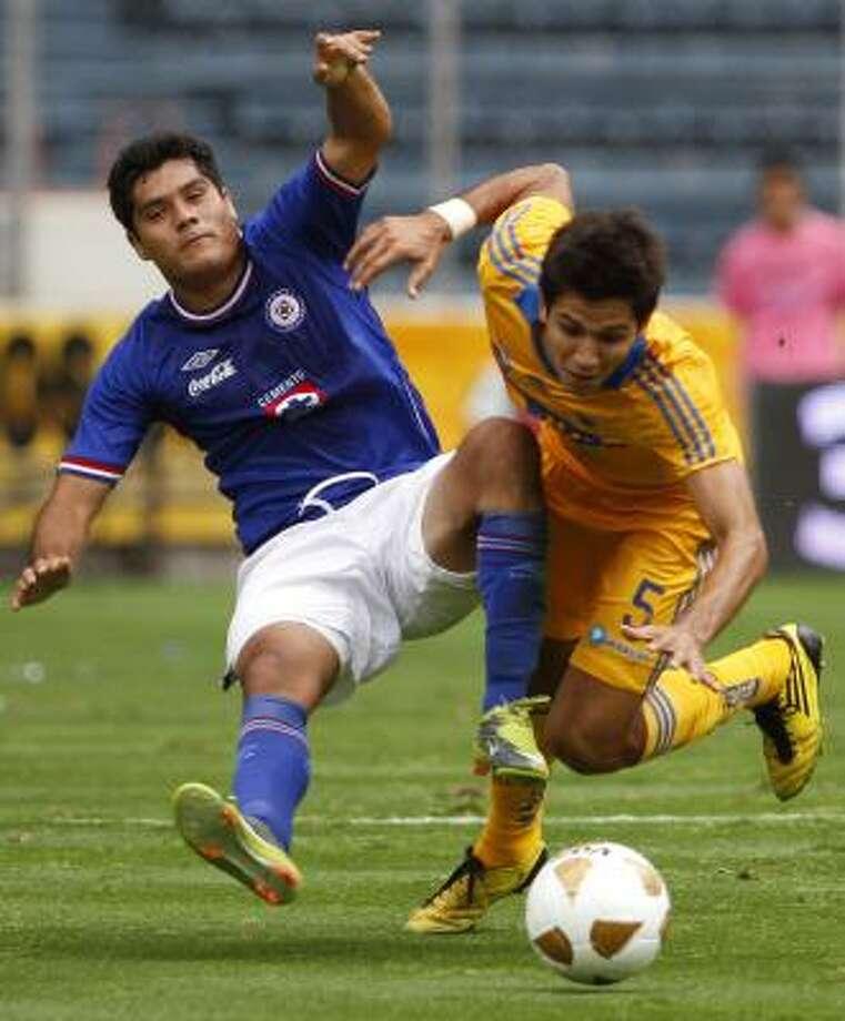 El goleador del Cruz Azul, Javier Orozco (izq.), es derribado por Jesús Granados en la victoria frente a Tigres. Photo: Claudio Cruz, AP