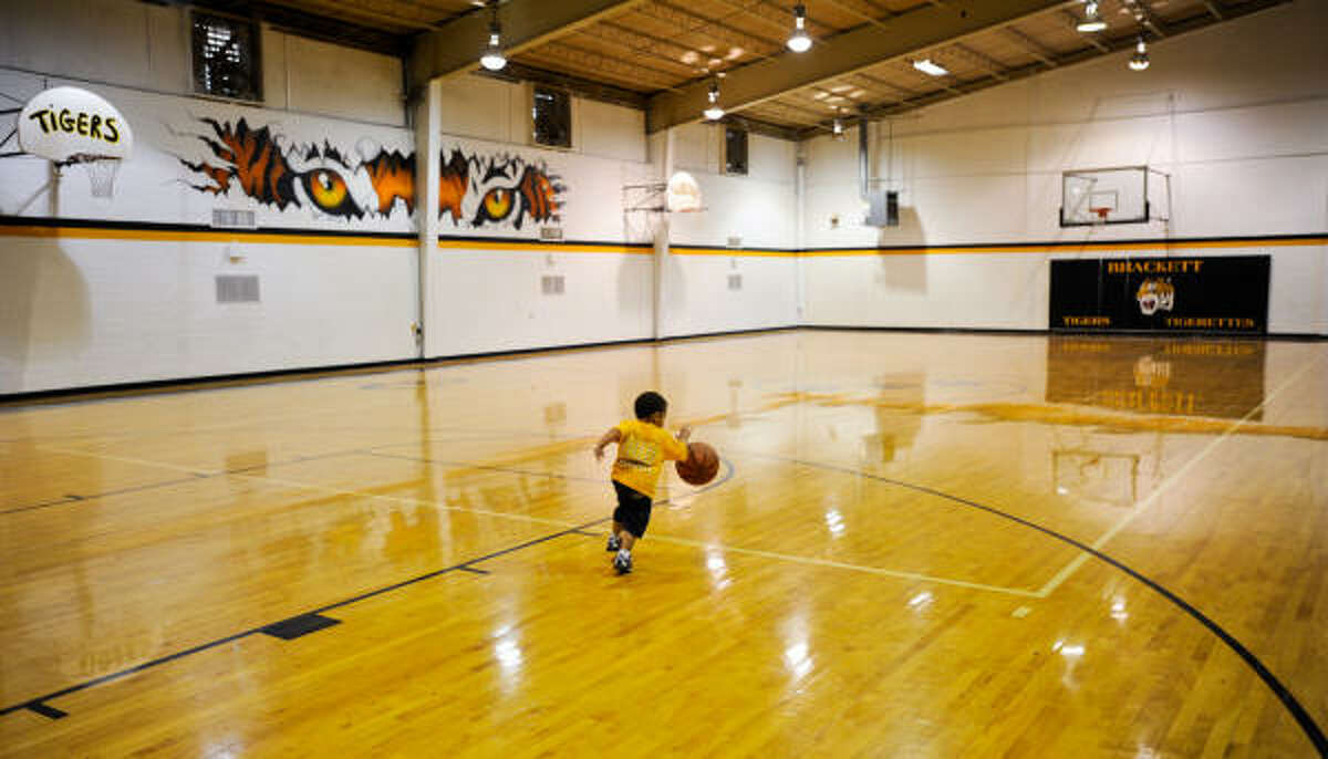 Hunter Williams, 2, runs the fast break inside the Brackett High School gymnasium. Shaquille O'Neal famously pulled down one of the gym's basketball goals during a game in the late 1980s.