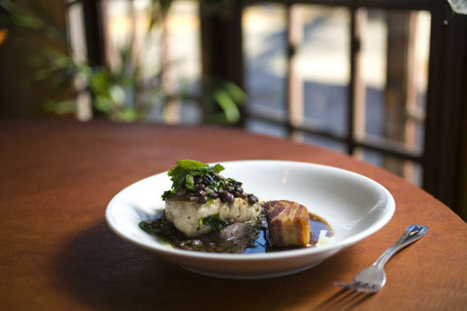Meaty, perfectly grilled mahi mahi came swimming in a gentle soy broth, touched with tamarind and jalapeño, with a cushion of slightly sweet pureed black beans supporting the fish. Photo: Nick De La Torre :, Chronicle