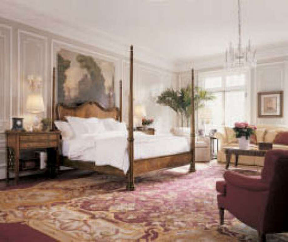 TALL, ELEGANT: A tall four-poster bed, wall art and added moldings are properly overscaled to suit a very large master bedroom.