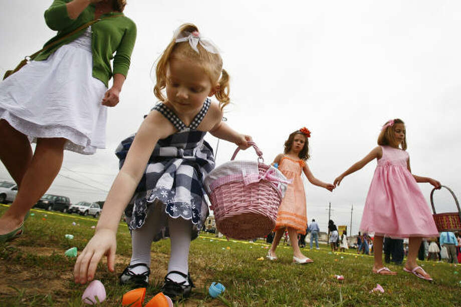 """Alanni Kraemer, 4, gathers Easter Eggs at The Woodlands Christian Center. Another 4-year-old egg hunter, Anthony Ventura, made the observation: """"You find an egg, and you put it in your basket."""" Photo: Michael Paulsen, Chronicle"""