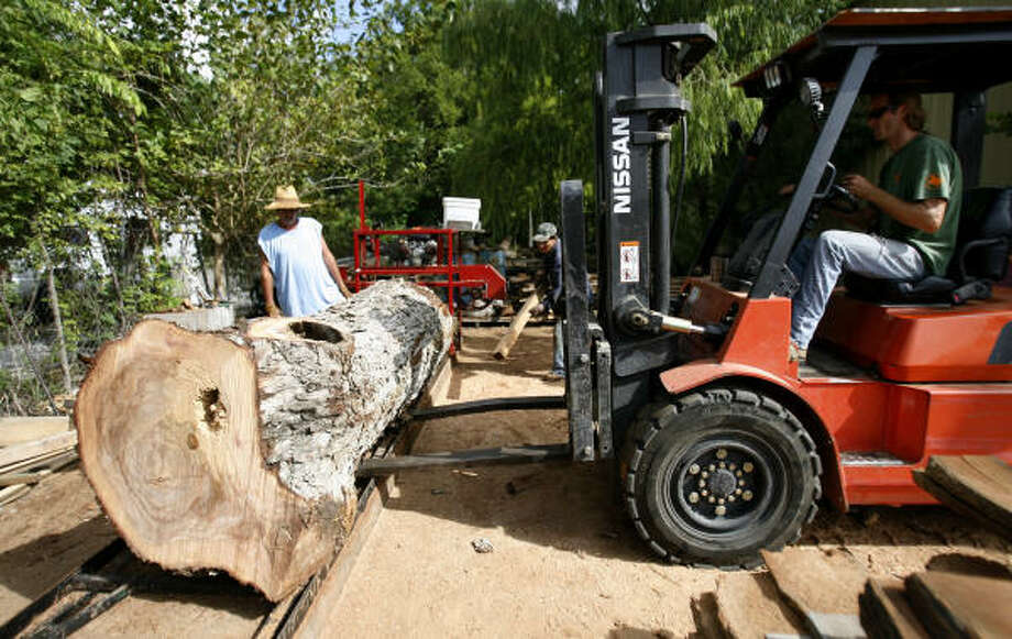 Brian Conner, owner of TruTimber, uses a forklift to adjust a tree trunk to be cut into two-inch thick slabs. Photo: Karen Warren, Chronicle