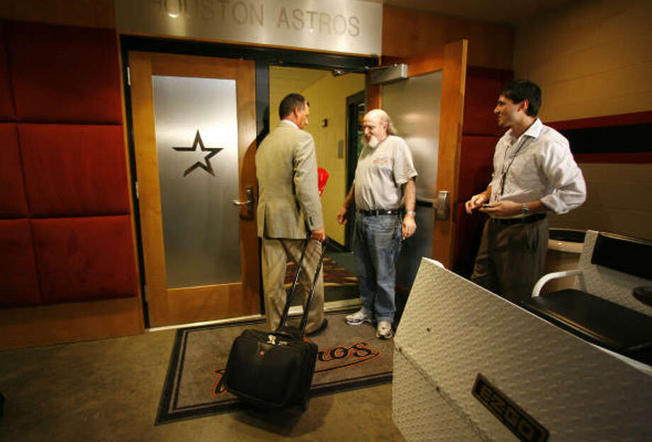 Al Pedrique, left, walks into the Astros clubhouse after finishing his interview and subsequent press conference. Photo: Karen Warren, Chronicle