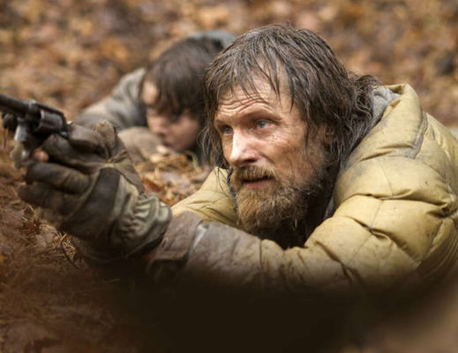 "In ""The Road,"" a boy and his father (Kodi Smit-McPhee, Viggo Mortensen) travel through a ravaged America, fending off looters and cannibals. Photo: MCT"