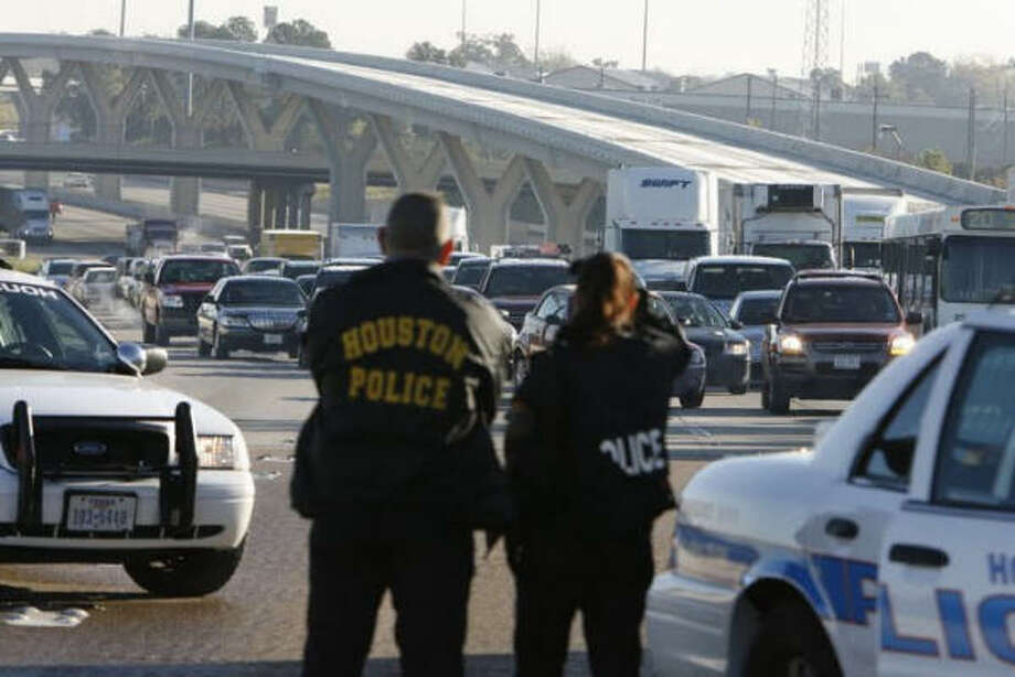 Houston police officers divert traffic from ice-covered lanes on Interstate 10 westbound at the Taylor street exit early Saturday morning. Photo: JAMES NIELSEN, Chronicle
