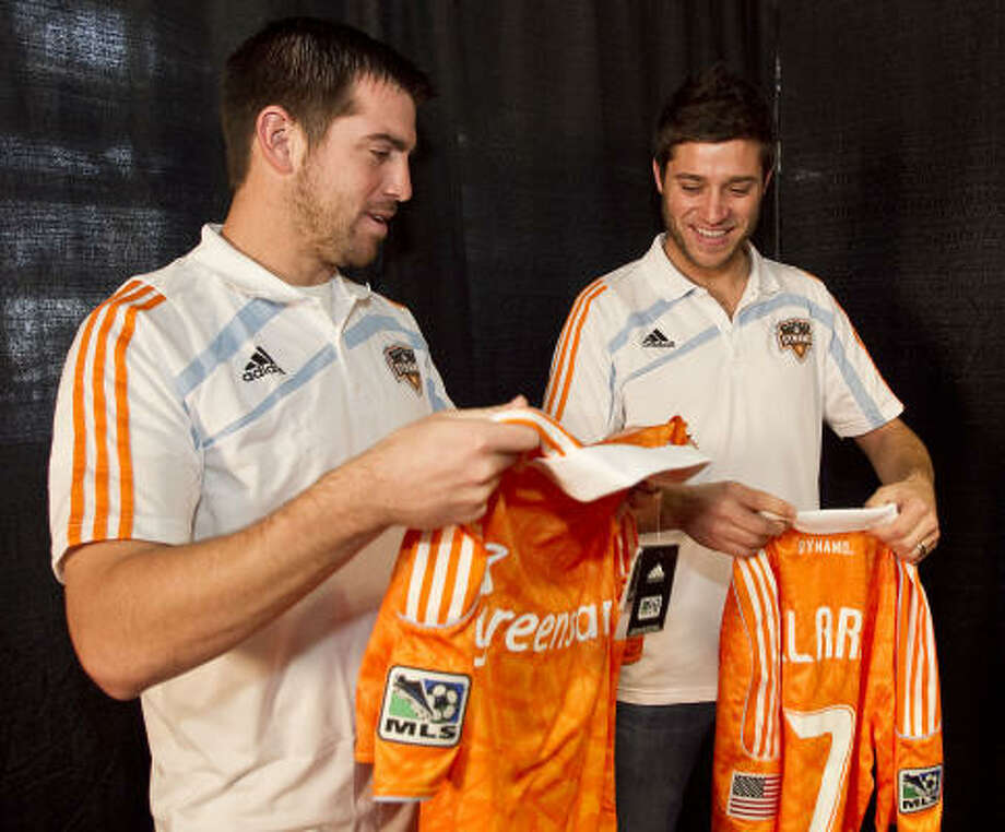 Jason Garey, left, and midfielder Colin Clark, a couple of Dynamo newcomers, look over their jerseys after Friday's news conference to introduce the team's newest players. Photo: James Nielsen, Chronicle