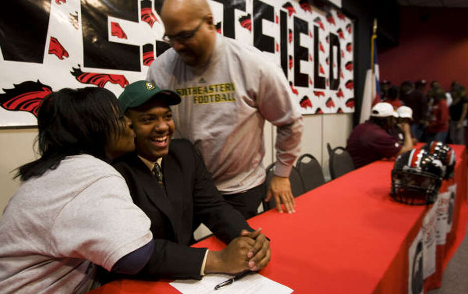 Lanita Hale, left, kisses her son, Westfield High School football player Jarrod Hale, on the cheek after he signed a letter of intent to play football at Southeastern Louisiana University on Wednesday. Photo: Brett Coomer, Chronicle