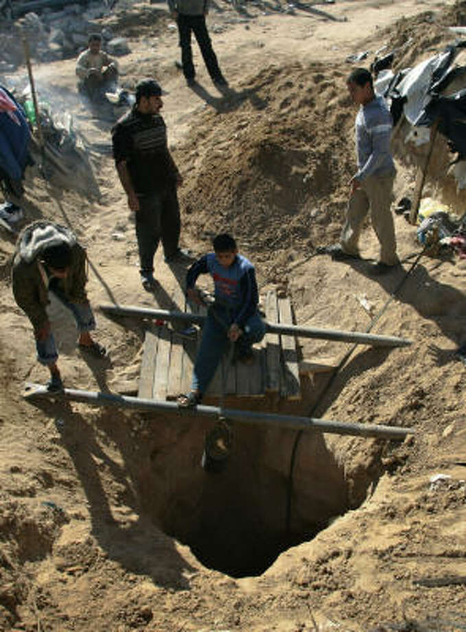DIGGING IN: Palestinians work Thursday on constructing new and repairing old smuggling tunnels, damaged during the Israeli military operation, that run under the border between Egypt and the southern Gaza Strip town of Rafah. Photo: LEFTERIS PITARAKIS, AP