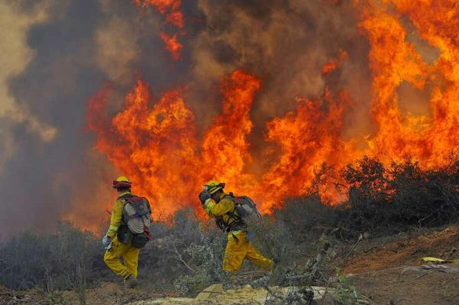 Firefighters watch as a brush fire spreads last month in the Santa Ynez Mountains about 100 miles north of Los Angeles. California is struggling with the most expensive wildfire season ever. Photo: PHIL KLEIN, ASSOCIATED PRESS FILE