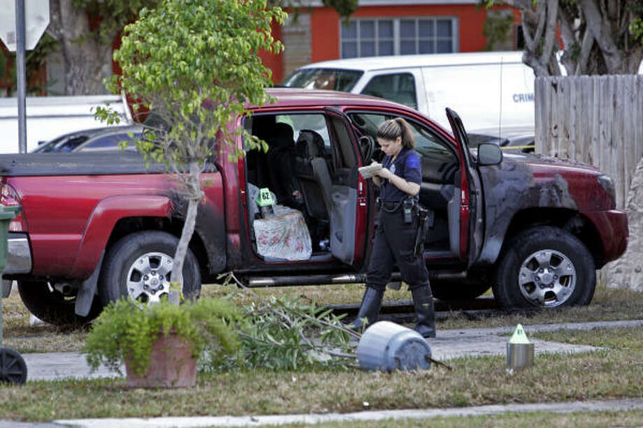 A Miami police crime scene investigator photographs the house where a man shot himself and set the house on fire after shooting four others at a family gathering at another location early Sunday. Photo: DAVID ADAME, AP