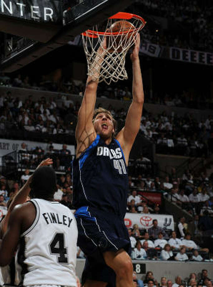 Mavericks forward Dirk Nowitzki (right) slams home a dunk against San Antonio's Michael Finley in Game 1. Photo: Ronald Martinez, Getty Images