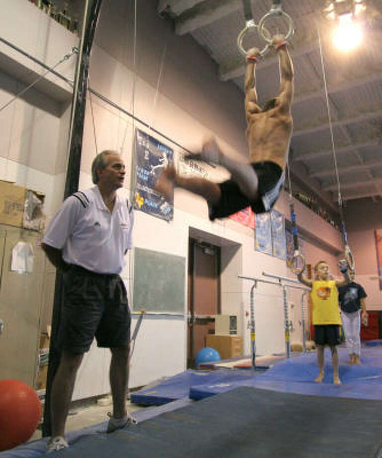 Jewish Community Center gymnastics director Tim Erwin watches as Joshua Steves, 14, practices on the rings. Joshua competed in the all-around finals at the United States Men's Junior Olympic National Championships this past spring. Photo: Jason Brown, For The Chronicle