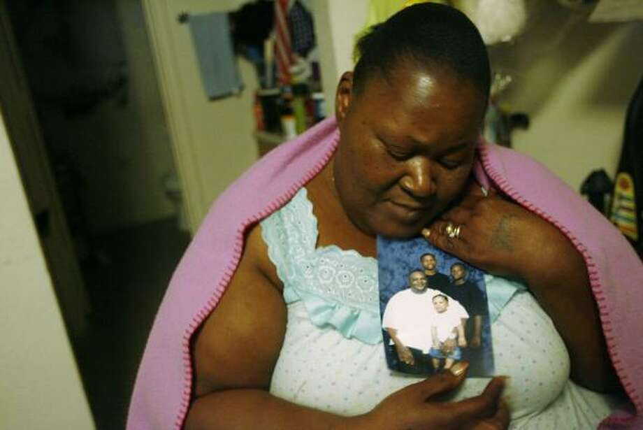 Joyce Emmitt holds a family picture of her son, Howard Dwayne Emmitt, and his stepson, Cardian Herd, 12, who died in a fire at their duplex in southeast Houston early Thursday. His stepdaughter, Sierra Herd, 9, was treated for smoke inhalation. Photo: MAYRA BELTRÁN, CHRONICLE
