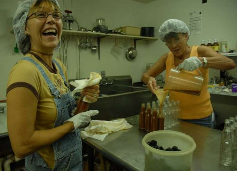 Becky Biles, left, wipes off a bottle of hot sauce as her mother, Barbara Johnson, fills bottles. Becky and husband Trevi Biles have focused hard on marketing their product. Photo: MEGAN TRUE PHOTOS, CHRONICLE