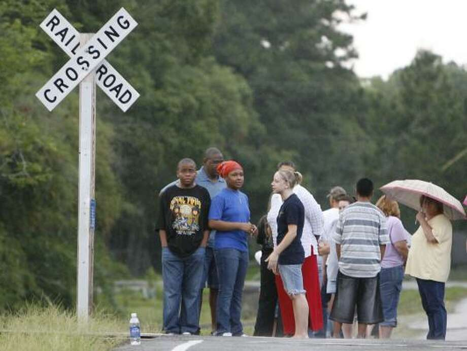 People gather June 14 at the railroad tracks where four teenagers died in a crash. Photo: JAMES NIELSEN, CHRONICLE FILE