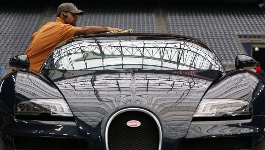 Jason Cavallo details a 2011 Bugatti Veyron 16.4 Super Sport as automobiles arrived before the start of the 8th Annual Classy Chassis Concours d' Elegance at Reliant Stadium in Houston. The vintage auto event, benefiting Shriners Hospitals for Children, begins Saturday June 11 and runs through Sunday June 12. Photo: Johnny Hanson, Houston Chronicle