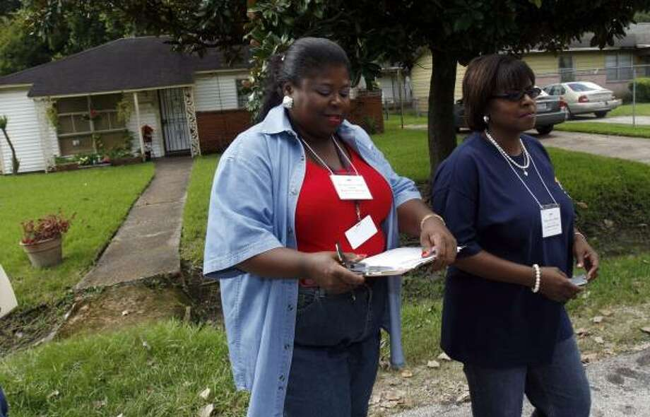 Kashmere High School Principal Dr. Charlotte Parker, left, and Diana Gibson-Johnson leave the home of one of 50 students who had not returned to school this year. Photo: JOHNNY HANSON, FOR THE CHRONICLE
