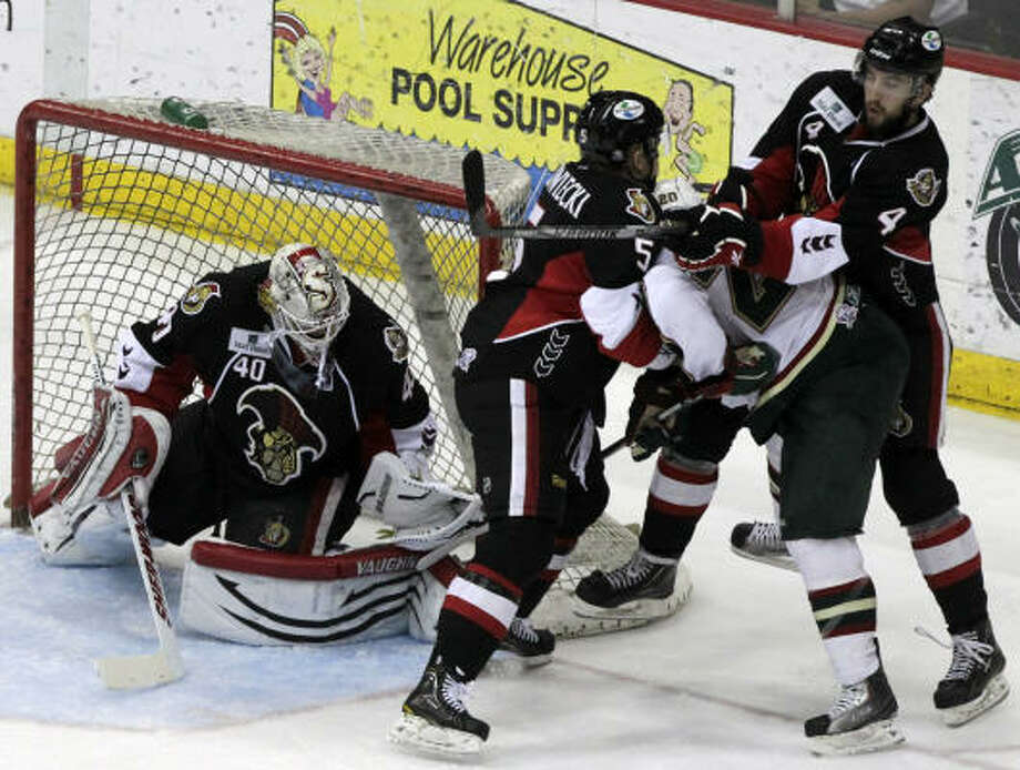 Aeros center Chad Rau (20) is sandwiched by Senators defensemen Mark Borowiecki (5) and Jared Cowen (4) as he tries to score on goalie Robin Lehner in the second period. Photo: Cody Duty, Chronicle