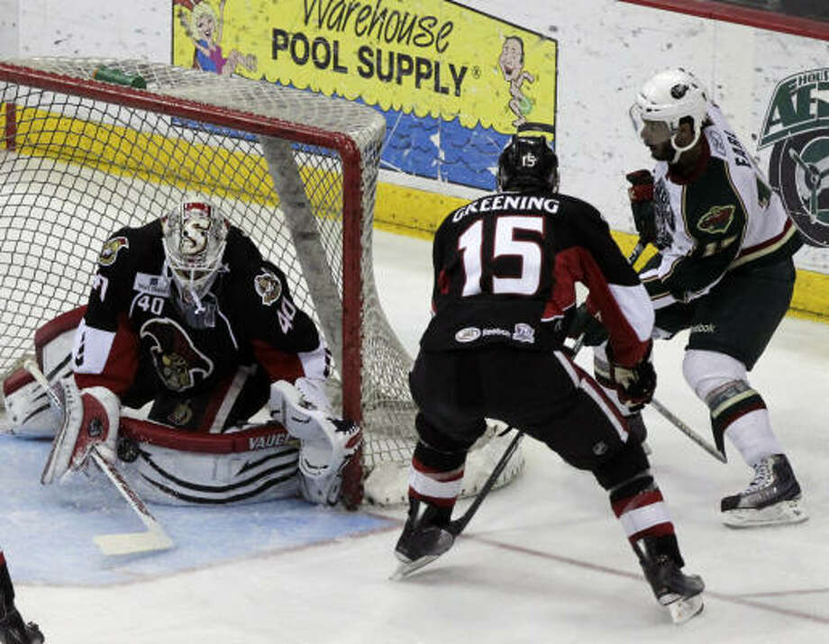 Senators goalie Robin Lehner stops a shot from Aeros left wing Robbie Earl, right, as left wing Colin Greening (15) looks on in the second period. Photo: Cody Duty, Chronicle