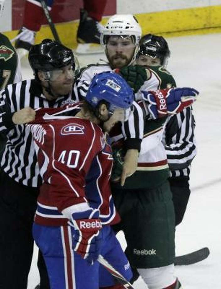 Officials break up a fight between Bulldogs center Gabriel Dumont (40) and Aeros defenseman Nate Prosser in the second period. Photo: Cody Duty, Chronicle