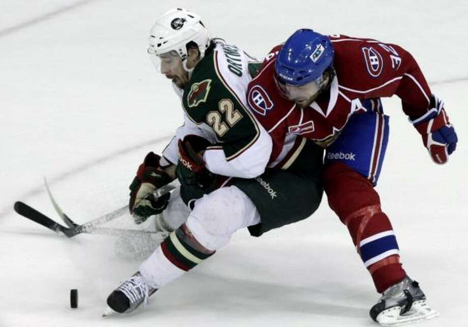 Aeros right wing Jed Ortmeyer (22) gets tangles up with Bulldogs defensemen Frederic St. Denis as they fight for possession in the first period. Photo: Cody Duty, Chronicle