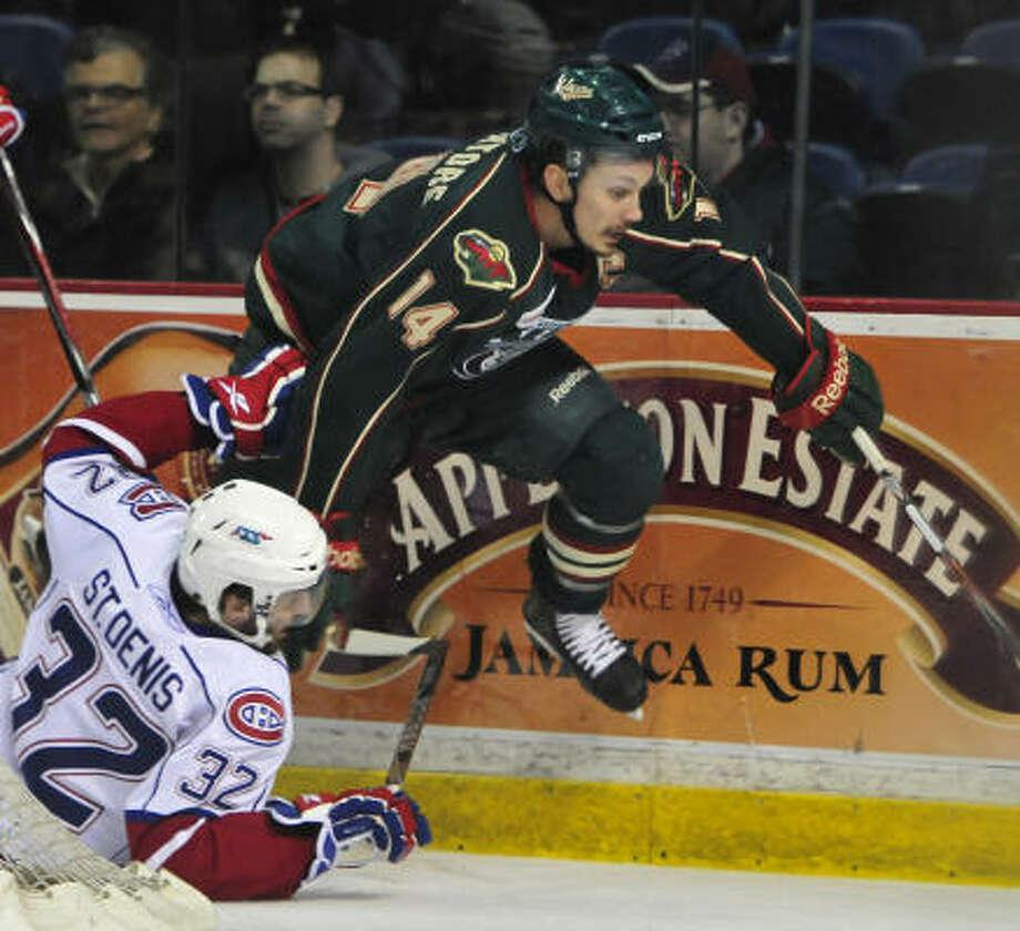 Aeros' Jon DiSalvatore jumps over Bulldogs' Frederic St. Denis. Photo: John Rennison, The Hamilton Spectator