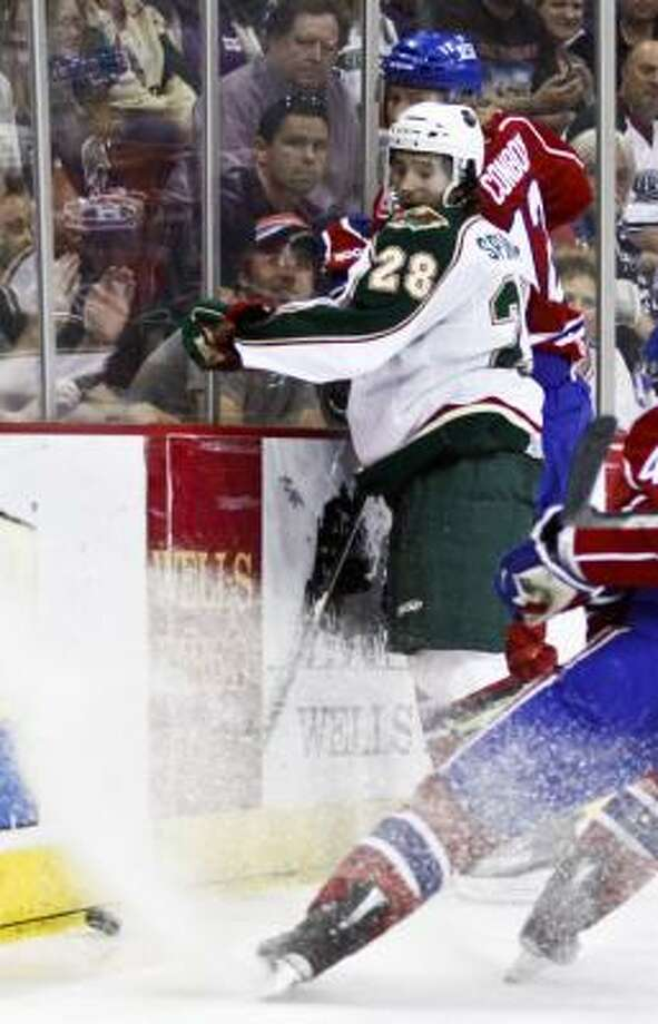 Aeros defender Jared Spurgeon (28) and Hamilton's Andrew Conboy fight for the puck. Photo: Eric Kayne, For The Chronicle