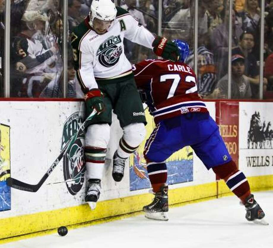 Aeros center Warren Peters, left, gets checked by Hamilton's Mathieu Carle. Photo: Eric Kayne, For The Chronicle