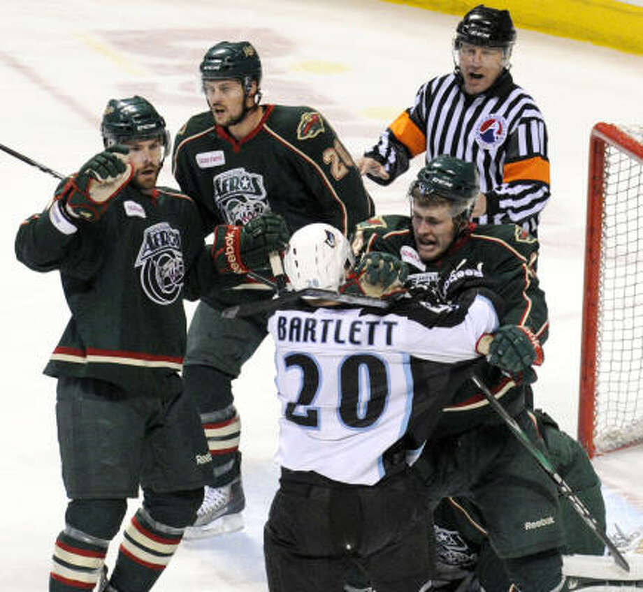 Milwaukee's Mike Bartlett (20) and Justin Falk get into a shoving match in front of the goal during the first period. Photo: Ernie Mastroianni, Milwaukee Journal Sentinel