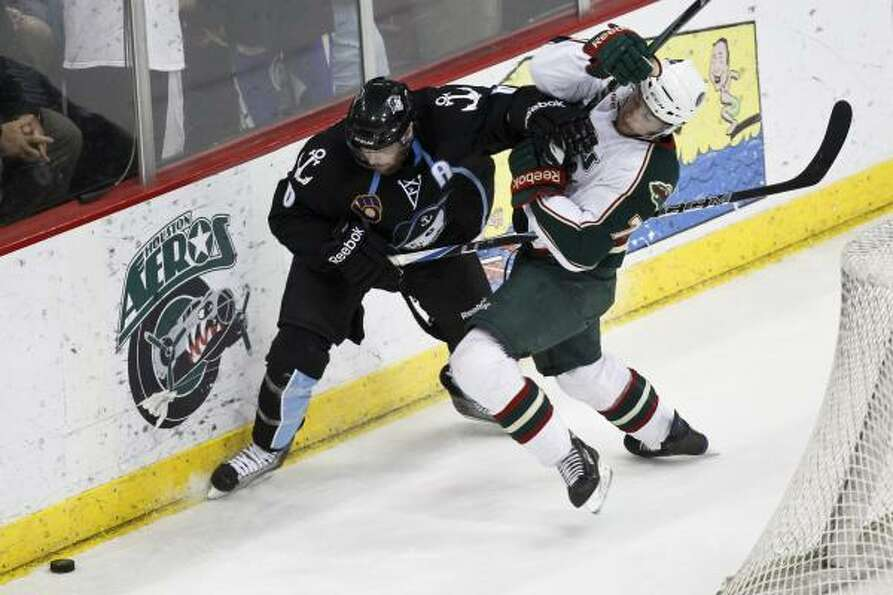 Aeros center Casey Wellman, right, battles with Admirals defenseman Aaron Johnson for possession of