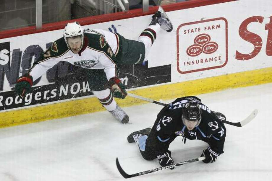 Aeros center Carson McMillan goes airborne after being tripped up by Admirals right wing Mike Bartlett. Photo: Michael Paulsen, Chronicle