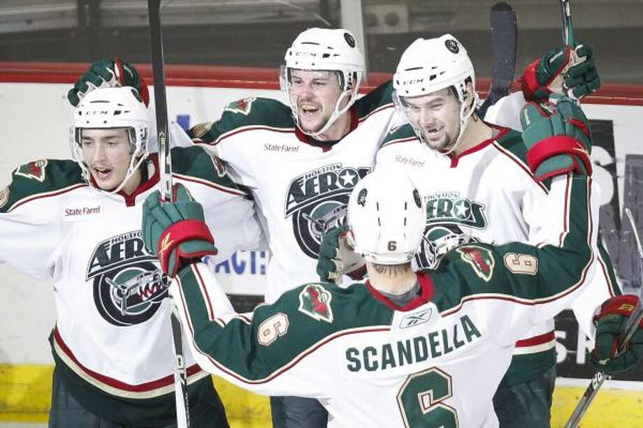 Aeros center Chad Rau, second from left, is congratulated by teammates after scoring the game-tying goal in the third period. Photo: Michael Paulsen, Chronicle
