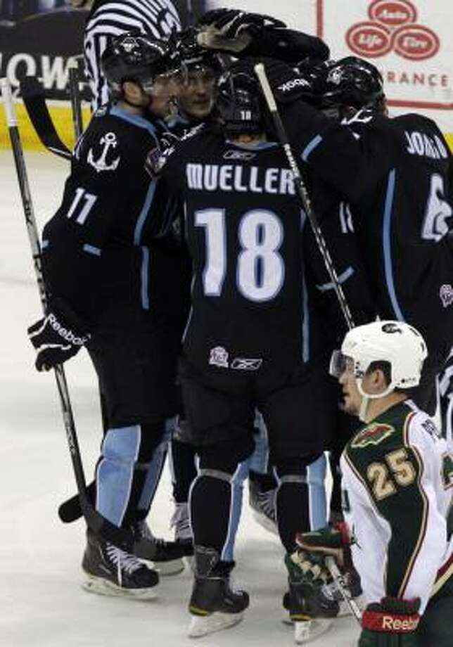 The Milwaukee Admirals celebrate after right wing Andreas Thuresson scored a goal as Houston Aeros center Warren Peters looks on. Photo: Cody Duty, Chronicle