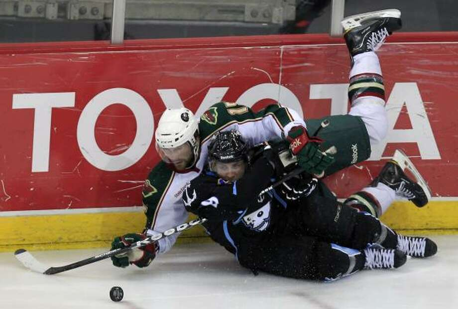 Aeros right wing Jarod Palmer is tripped up by Milwaukee's Gabriel Bourque in the third period. Photo: Cody Duty, Chronicle