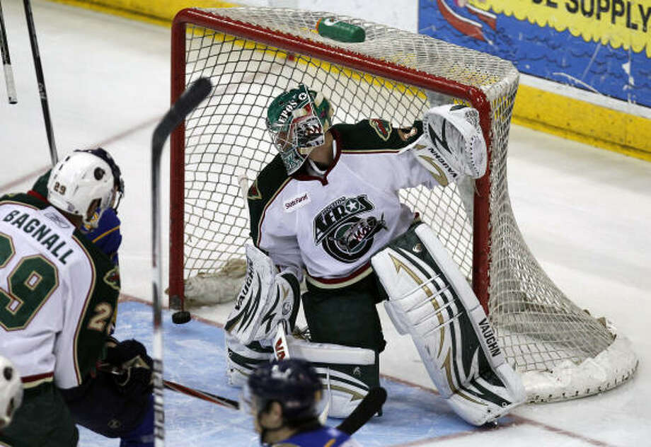 A shot from Peoria Rivermen right wing Adam Cracknell (19) squeezes by Aeros goalie Matt Hackett. Photo: Cody Duty, Chronicle