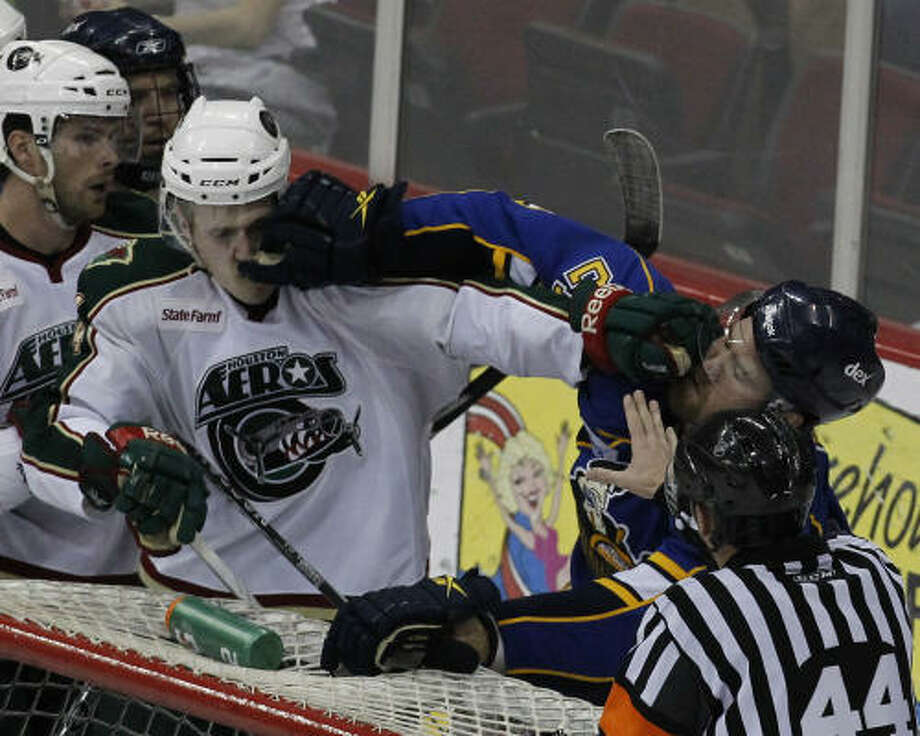 Aeros defenseman Justin Falk (44), left, and Peoria Rivermen right wing Graham Mink (21) punch each other after a shot attempt from Peoria during the third period. Photo: Cody Duty, Chronicle