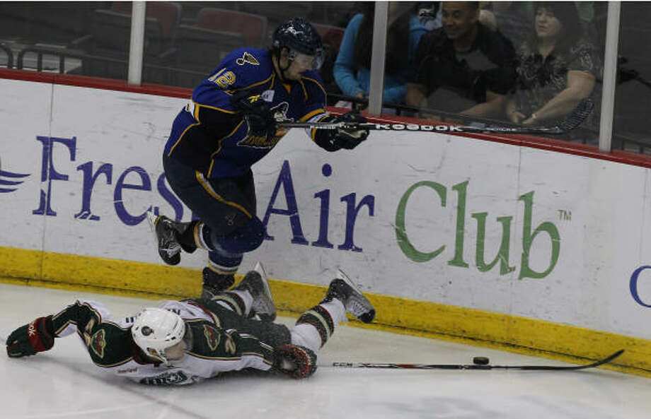 Aeros defenseman Maxim Noreau (26) (bottom) is tripped up as he fights for possession of the puck. Photo: Cody Duty, Chronicle