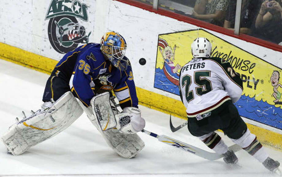 Peoria Rivermen goalie Jake Allen (35) attempts to take possession from Houston Aeros center Warren Peters (25). Photo: Cody Duty, Chronicle