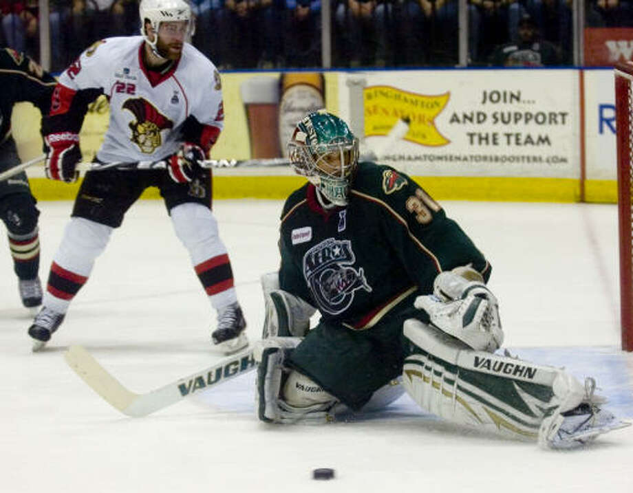 Binghamton Senators' (22) Ryan Potulny pressures Houston Aeros' (31) Matt Hackett, who deflects the puck in the first period. Photo: REBECCA CATLETT/ Press & Sun-Bulletin