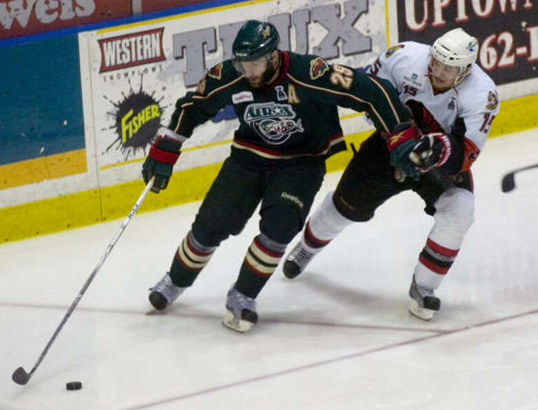Binghamton Senators' (15) Colin Greening pressures Houston Aeros' (29) Drew Bagnall in the third per